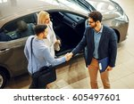 young couple shaking hands with ... | Shutterstock . vector #605497601