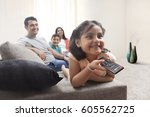 smiling girl watching tv with... | Shutterstock . vector #605562725