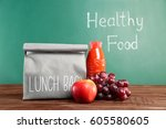 lunch bag on wooden tabletop... | Shutterstock . vector #605580605