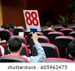 holding a auction paddle | Shutterstock . vector #605962475