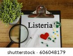 Small photo of Medical concept : Listeria text ,magnifier,pills and syringe on wooden background