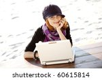 Portrait of red-haired girl with laptop at beach. - stock photo