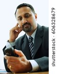 Small photo of Businessman looking at PDA phone
