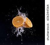 cut orange in water splash on... | Shutterstock . vector #606344564