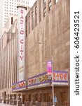 Small photo of NEW YORK, USA - JULY 4, 2013: People walk past Radio City Music Hall at 6th Avenue in New York. Radio City exists since 1932 and is registered in U.S. National Register of Historic Places.