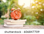 red alarm clock and book on... | Shutterstock . vector #606847709