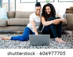 Small photo of Smiling lesbian couple sitting on rug and using laptop in living room