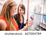 two beautiful women selecting a ... | Shutterstock . vector #607004789