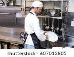 handsome employee doing dishes... | Shutterstock . vector #607012805