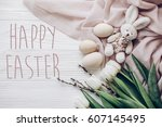 happy easter text greeting card sign on stylish easter eggs and willow buds and rabbit and white tulips on rustic wooden background and fabric flat lay.  concept with space for text, top view