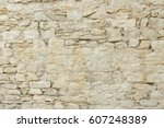 Small photo of Old beige stone wall background texture close up