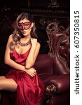 Small photo of Charming elegant woman in beautiful red dress and masquerade mask is sitting in a chair in a luxury apartment. Classic vintage interior. Beauty, fashion.