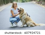 Stock photo girl walking in the park with his dog girl playing with a dog at the beach and in the park 607924721