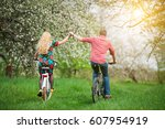 active couple ride bicycles in... | Shutterstock . vector #607954919