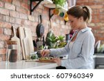 home. young woman in kitchen | Shutterstock . vector #607960349