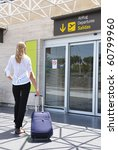 Girl with a suitcase entering airport - stock photo