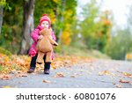 Adorable toddler girl with teddy bear outdoors on beautiful autumn day - stock photo