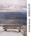 Small photo of Panoramic view from the top of the Nordkette mountain to the city of Innsbruck. Wooden bench on the observation deck is covered with frost, a strong snow, a blizzard and city below in a snowy shroud.