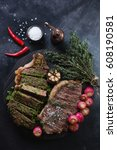 Small photo of Above view of grilled striploin steaks served with roasted radishes and chimichurri, studio shot