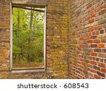 This is  a shot of a really old brick wall with a window with some woods in the background. - stock photo