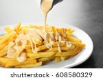 pouring cheese sauce on french... | Shutterstock . vector #608580329