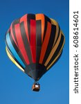 Small photo of Hot air balloon, colorful aerostat with people on clear blue sky