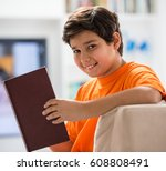 kid with book at home | Shutterstock . vector #608808491