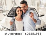 Small photo of Visiting car dealership. Beautiful couple is holding a key of their new car, looking at camera and smiling