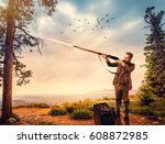Small photo of Duck hunter in hunting clothing aims an old rifle