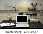Stock photo a cat in a home office peeping behind a laptop screen on a desk with stationery equipment and 60910537
