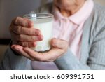 senior woman holding glass of... | Shutterstock . vector #609391751