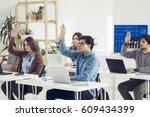 college students raising hands... | Shutterstock . vector #609434399