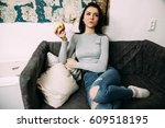 Small photo of Pretty woman eats apple sitting on black chair