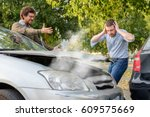Small photo of Two men arguing after a car accident on the road