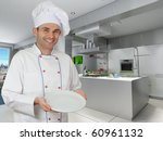 Smiling chef holding an empty plate in a modern kitchen - stock photo