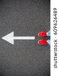 Small photo of Sneakers on the asphalt road with drawn direction arrow