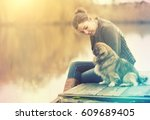 woman with dog at lake | Shutterstock . vector #609689405