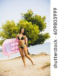 Small photo of Young slim brunette woman sunbathe with an air mattress on the beach
