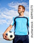 Handsome European man holding a football outdoors - stock photo
