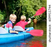 two boys kayaking on the river. ... | Shutterstock . vector #609911744