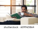 Indian Male Reading Book On Sofa