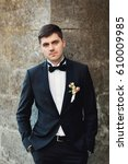Small photo of Handsome groom in black suit with tose boutonniere holds his hands in the pockets posing outside