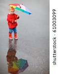 Toddler girl with colorful umbrella, beautiful reflection on puddle - stock photo