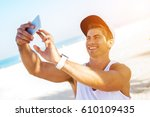 Small photo of Guy in sport outfit with tracker on left hand checking fitness result on phone looking glad making selfie taking photo.