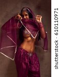 Small photo of Eastern beautiful brunette belly-dancer woman in afghani pants, purdah and adornment.