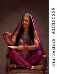 Small photo of Eastern beautiful brunette woman in afghani pants, purdah and adornment have a tea armut