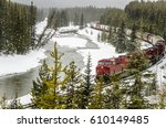 Small photo of Goods Train Pulled By Red Diesel Locomotives on Winding Track along a Frozen River on a Snowing Winter Day. Banff National Park, AB, Canada.