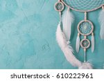 Small photo of Mint cream dream catcher on turquoise textured background. Texture of concrete.
