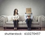 Stock photo shy man sitting next to a woman with his head covered by a cardboard box 610270457