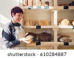 bakery employee holding a loaf... | Shutterstock . vector #610284887